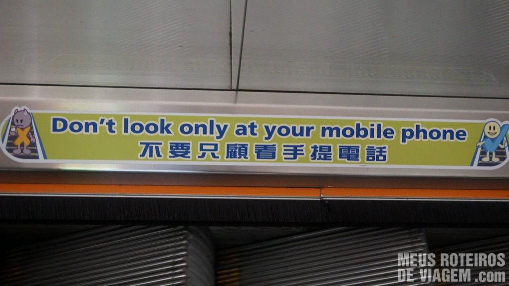 """Aviso na escada rolante do aeroporto: """"Não olhe somente para o seu telefone celular"""""""